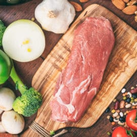 Raw pork fillet on wooden background. Fresh, healthy, uncooked pig meat on wood cutting board